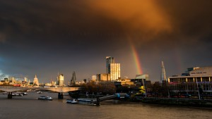 A fleeting moment of light during heavy rain in London town, with the Shard sandwiched between a double rainbow.